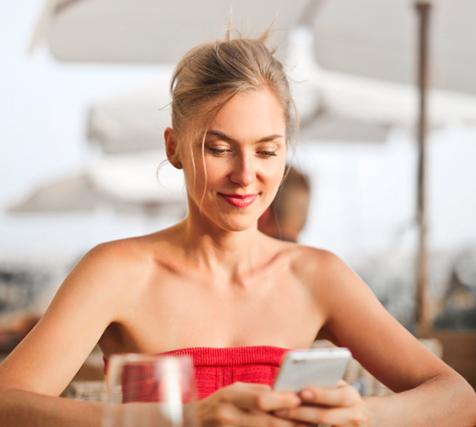 Kobieta korzystająca z płatności SMS Premium Rate na smartfonie